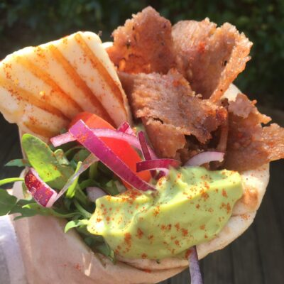 Wrap with gyros kebab, halloum, avocado sauce, vegetables and onions