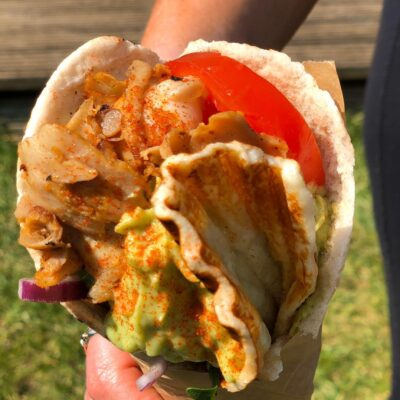 Gluten free wrap with meat, halloumi, avocado sauce, tomatoes, vegetables, onions